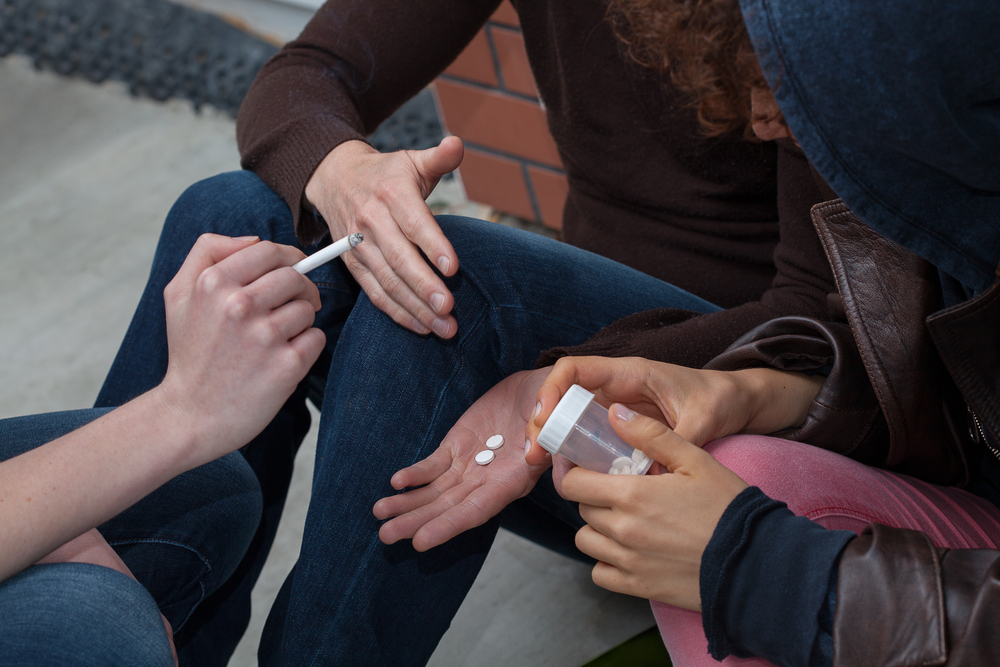 Drug users smoking and taking some pills